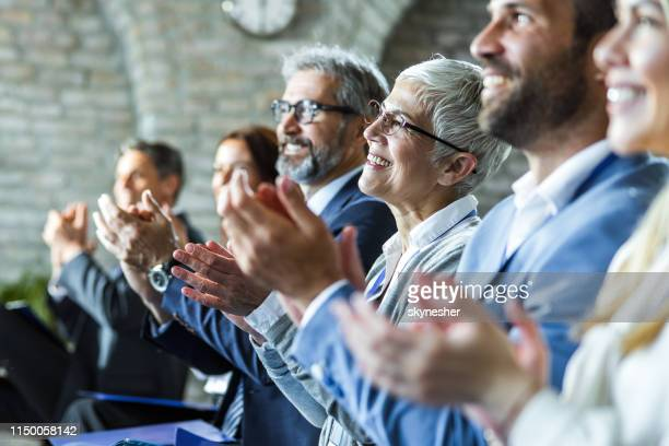 happy entrepreneurs applauding on education event in board room. - attending stock pictures, royalty-free photos & images