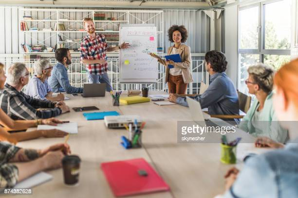 Happy entrepreneurs presenting their coworkers new business strategy on a meeting.