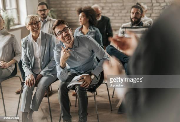 Happy entrepreneurs talking to public speaker on a seminar in a board room.
