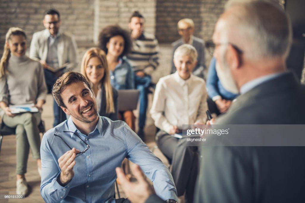 Glückliche Unternehmer im Gespräch mit öffentlicher Redner auf einem Seminar in einem Konferenzraum. : Stock-Foto