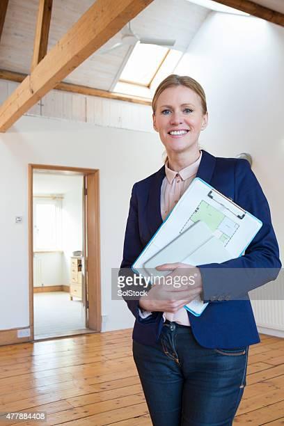 Heureux Agent immobilier tenant des papiers et tablette numérique