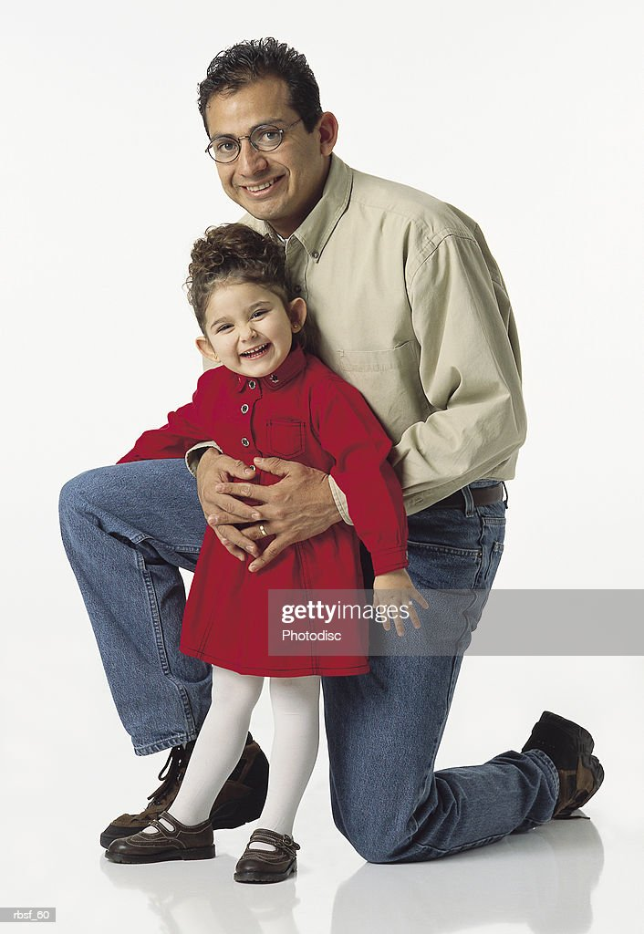 happy ethnic dad with arms around his young daughter in red kneels behind her : Foto de stock