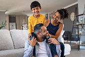 Happy ethnic family playing together at home