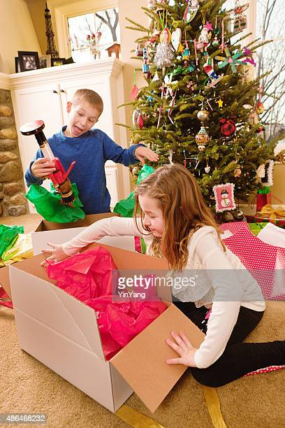 Happy Excited Children Opening Christmas Presents in Front of Tree