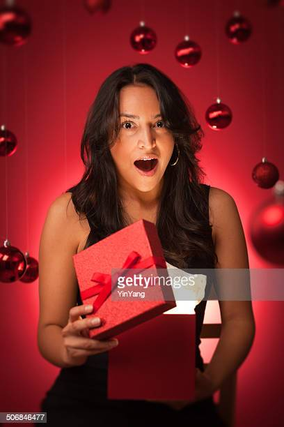Happy Excited Hispanic Model Opening Magical Christmas Gift