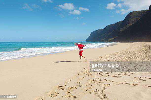 happy excited jumping santa claus on hawaiian beach vacation hz - hawaii christmas stock pictures, royalty-free photos & images