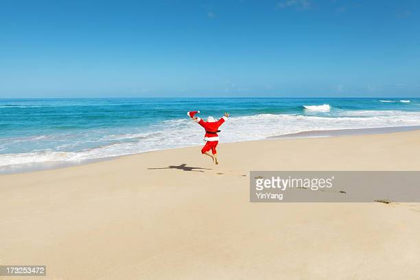 happy excited jumping santa claus on tropical beach vacation hz - beach christmas stock pictures, royalty-free photos & images