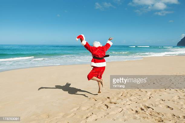happy excited jumping santa claus on  tropical beach vacation - hawaii christmas stock pictures, royalty-free photos & images