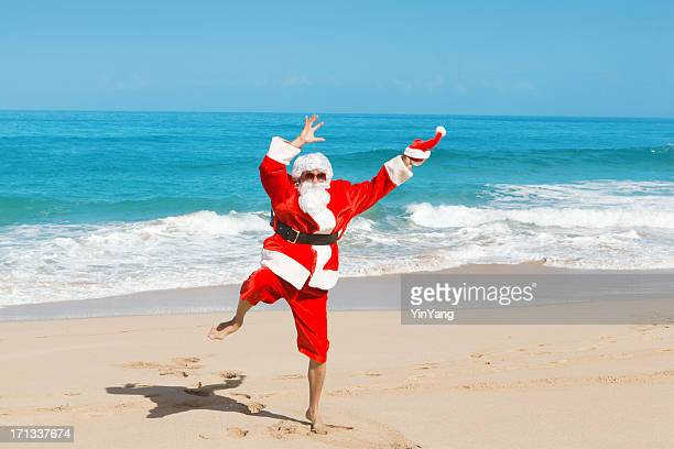 happy excited jumping santa claus on  tropical beach vacation-2 - hawaii christmas stock pictures, royalty-free photos & images