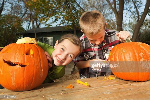 Felice eccitato bambini Carving Halloween Pumpkins insieme all'aperto in autunno