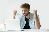 Happy excited man celebrating online win result looking at laptop