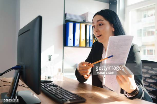 happy executive pointing contract on videocall at office - lawyer stock pictures, royalty-free photos & images