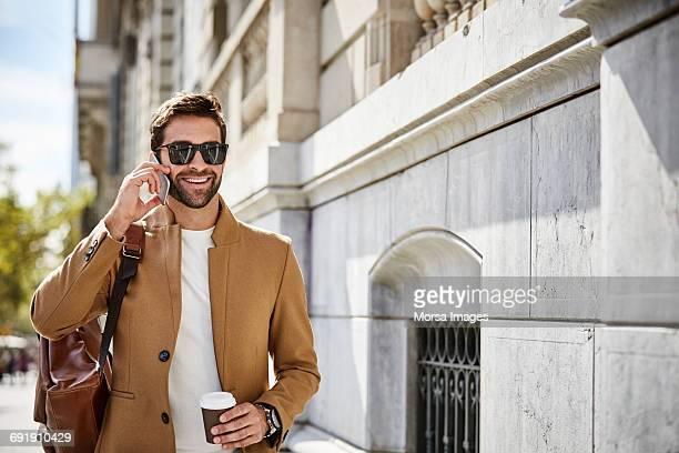 happy executive talking on phone while holding cup - coat stock pictures, royalty-free photos & images