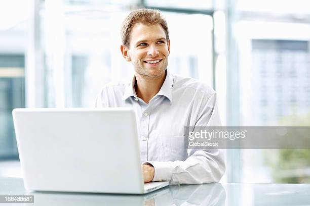 Happy executive working on his laptop