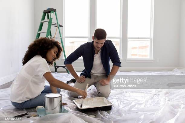 happy expectant couple paint nursery - painting activity stock pictures, royalty-free photos & images