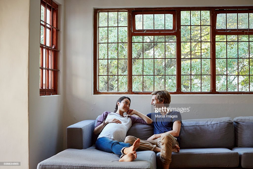 Happy expectant couple sitting on sofa at home : Stock Photo