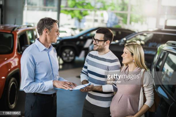 happy expecting couple communicating with manager while buying a car in a showroom. - car salesperson stock pictures, royalty-free photos & images