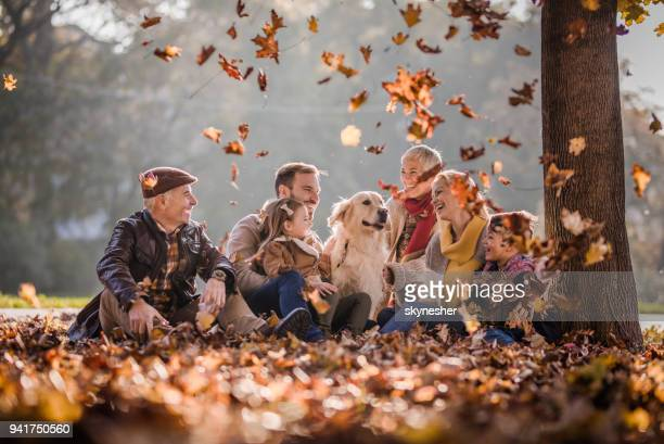 Happy extended family and golden retriever among autumn leaves at the park.