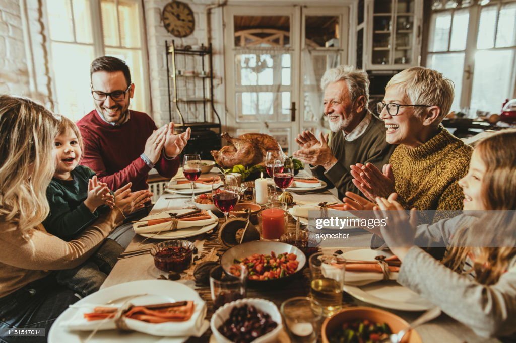 Happy extended family applauding during Thanksgiving meal at dining table. : Stock Photo