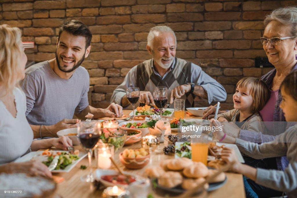 Feliz estendido a família comunicar durante um jantar na mesa de jantar. : Foto de stock