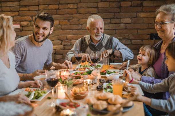 happy extended family communicating while having a dinner at dining table. - dinner table stock pictures, royalty-free photos & images