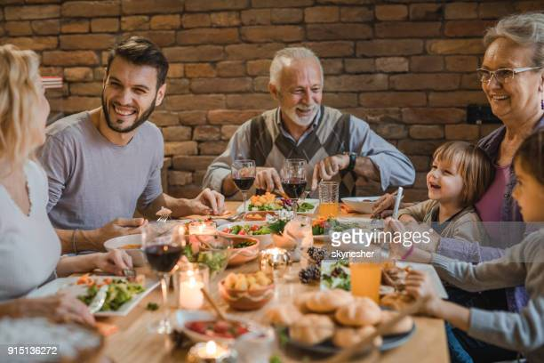 happy extended family communicating while having a dinner at dining table. - dinner table stock photos and pictures