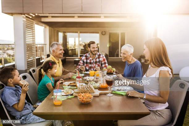 happy extended family enjoying in a lunch time on the balcony. - penthouse girls stock pictures, royalty-free photos & images