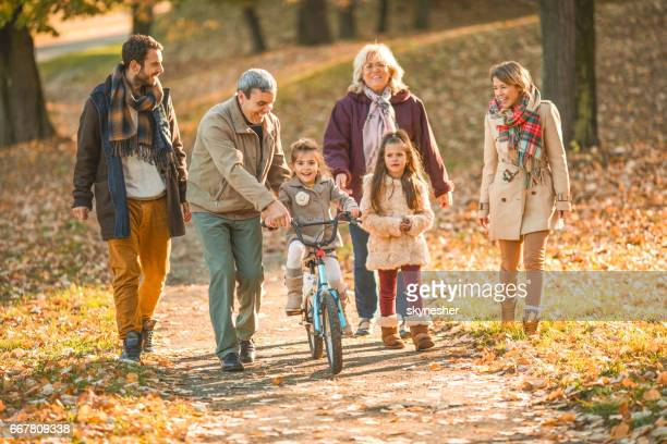 happy extended family enjoying in autumn day at the park. - multigenerational family stock photos and pictures
