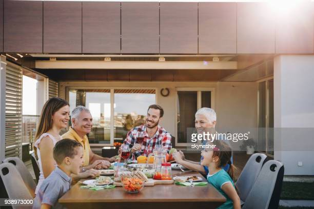happy extended family enjoying in lunch on the balcony. - penthouse girls stock pictures, royalty-free photos & images