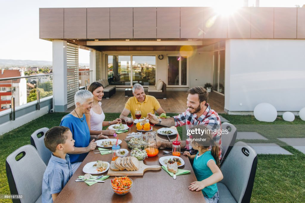 Happy extended family enjoying in lunch time on a penthouse patio. : Stock Photo