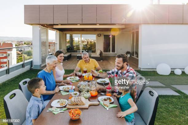 happy extended family enjoying in lunch time on a penthouse patio. - penthouse girls stock pictures, royalty-free photos & images