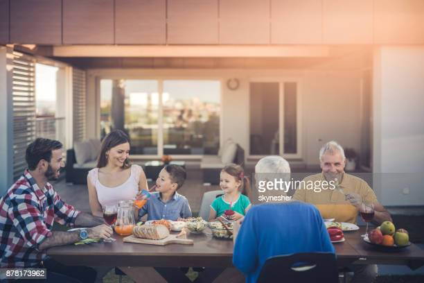 happy extended family enjoying in lunch time on the balcony. - penthouse girls stock pictures, royalty-free photos & images