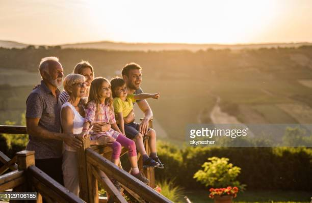 happy extended family enjoying on a terrace at sunset. - multi generation family stock pictures, royalty-free photos & images