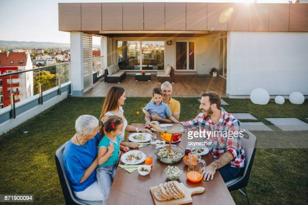 happy extended family having a lunch on balcony in front of their penthouse. - penthouse girls stock pictures, royalty-free photos & images