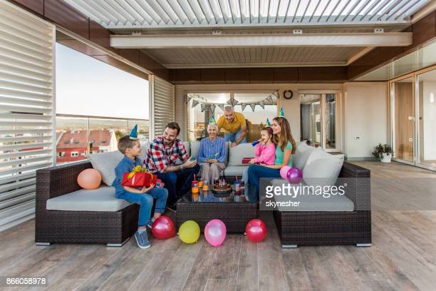 happy extended family having fun during birthday party on a penthouse patio. - penthouse girls stock pictures, royalty-free photos & images