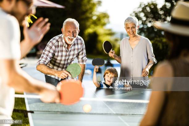happy extended family having fun while playing table tennis in the backyard. - table tennis stock pictures, royalty-free photos & images