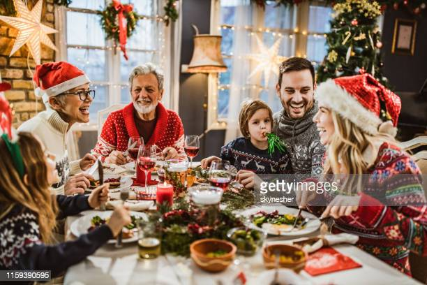 happy extended family having new year's lunch at dining table. - evening meal stock pictures, royalty-free photos & images