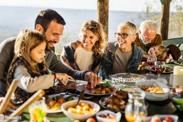 happy extended family having their lunch on a terrace. - lunch stock pictures, royalty-free photos & images
