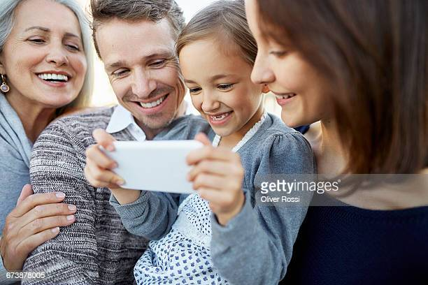 Happy extended family looking at cell phone