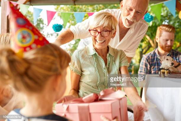 happy extended family on a garden birthday party - gift lounge stock-fotos und bilder
