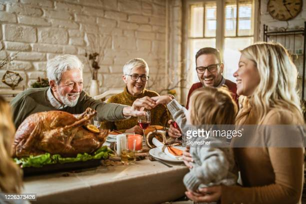 happy extended family on thanksgiving meal at dining table. - thanksgiving stock pictures, royalty-free photos & images