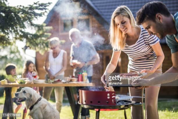 famille élargie heureuse préparant le barbecue dans l'arrière-cour. - grillade photos et images de collection