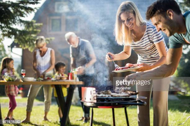 happy extended family preparing barbecue in the backyard. - grilling stock pictures, royalty-free photos & images