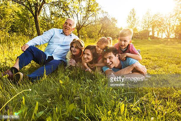 Happy extended family relaxing in the grass during springtime.