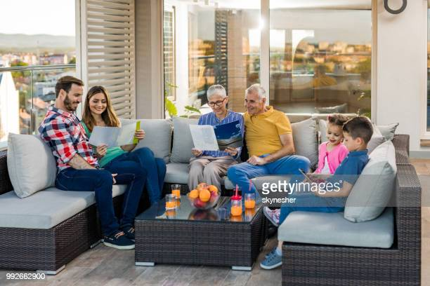 happy extended family relaxing on sofa at penthouse patio. - penthouse girls stock pictures, royalty-free photos & images