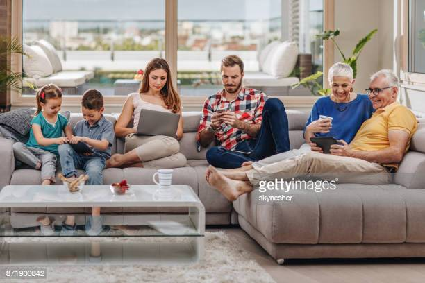 happy extended family relaxing on the sofa and using wireless technology. - penthouse girls stock pictures, royalty-free photos & images