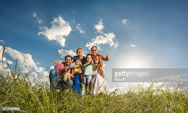 Happy extended family showing thumbs up in a meadow.