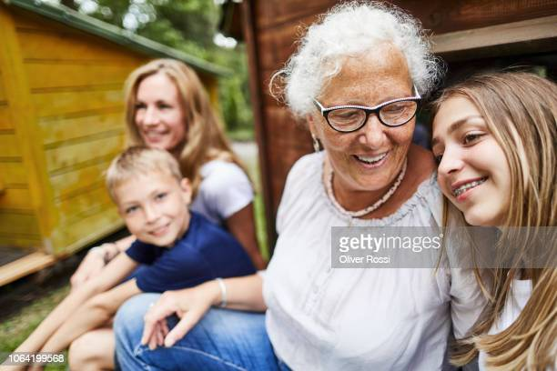 happy extended family sitting at a hut in an amusement park - teenager alter stock-fotos und bilder