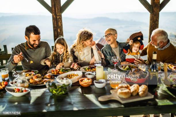 happy extended family talking during lunch on a terrace. - eating stock pictures, royalty-free photos & images