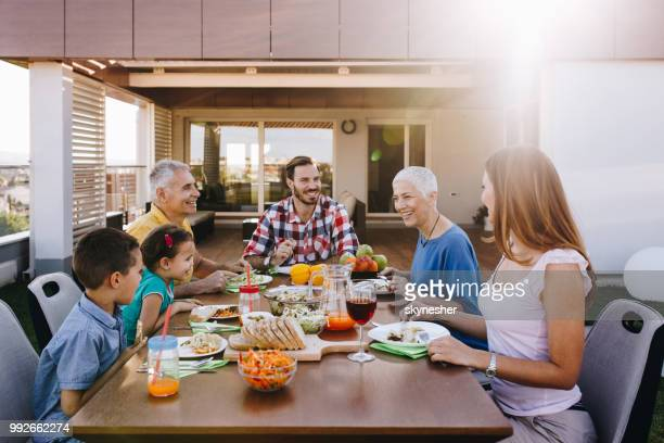 happy extended family talking during lunch on the balcony. - penthouse girls stock pictures, royalty-free photos & images